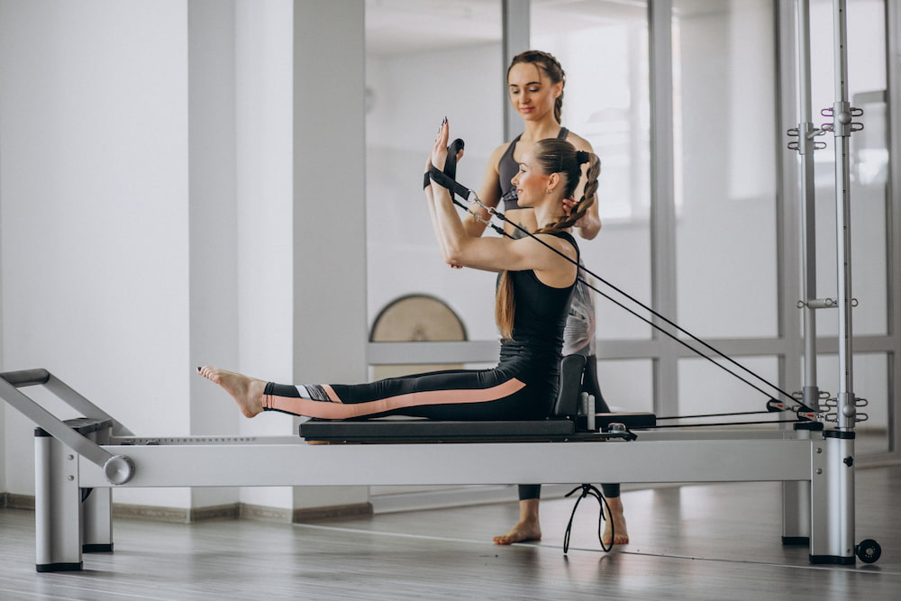 mulher com instrutora praticando pilates